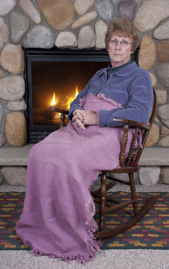 Mature Senior Woman Sad Face Rocking Chair, Fire. Mature senior woman has a sad, serious expression on her face and she sits and rests in her rocking chair royalty free stock photos
