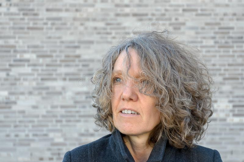 Mature serious woman with curly tousled hair. Mature serios woman with curly tousled hair looking off to the side as she poses in front of a grey brick wall with stock photos