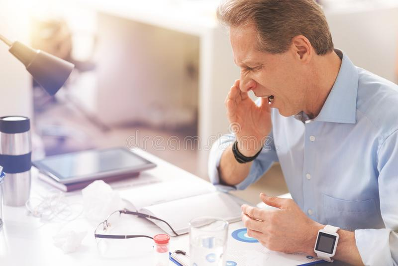 Mature sick man coughing in the office royalty free stock photos