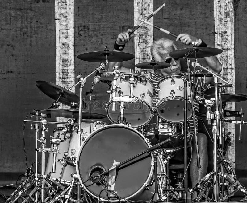 Mature silver haired drummer - black & white - action shot taken in Chippenham Park, Wiltshire, UK stock photo