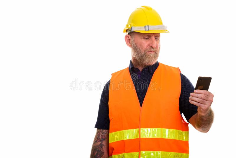 Mature skäggig manbyggnadsarbetare som använder mobiltelefonen royaltyfria foton