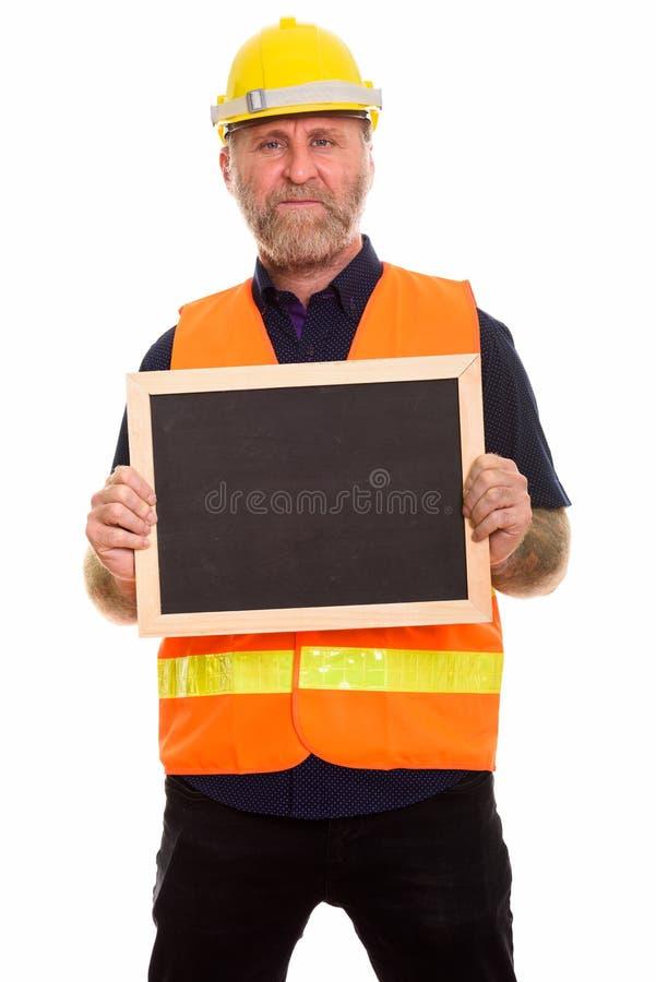 Mature skäggig manbyggnadsarbetare som rymmer den tomma svart tavla royaltyfri bild