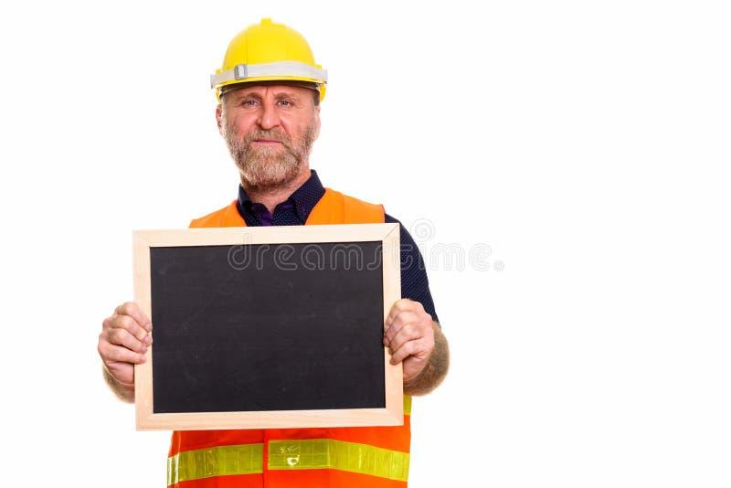 Mature skäggig manbyggnadsarbetare som rymmer den tomma svart tavla arkivbild