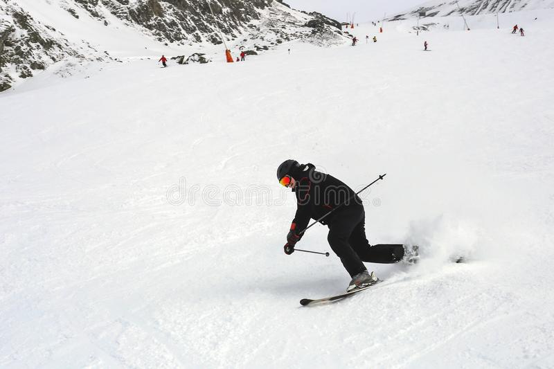 Mature skier fallen during downhill at ski resort in winter. Accident at ski slope due to unfasten ski binding. Extreme winter stock image