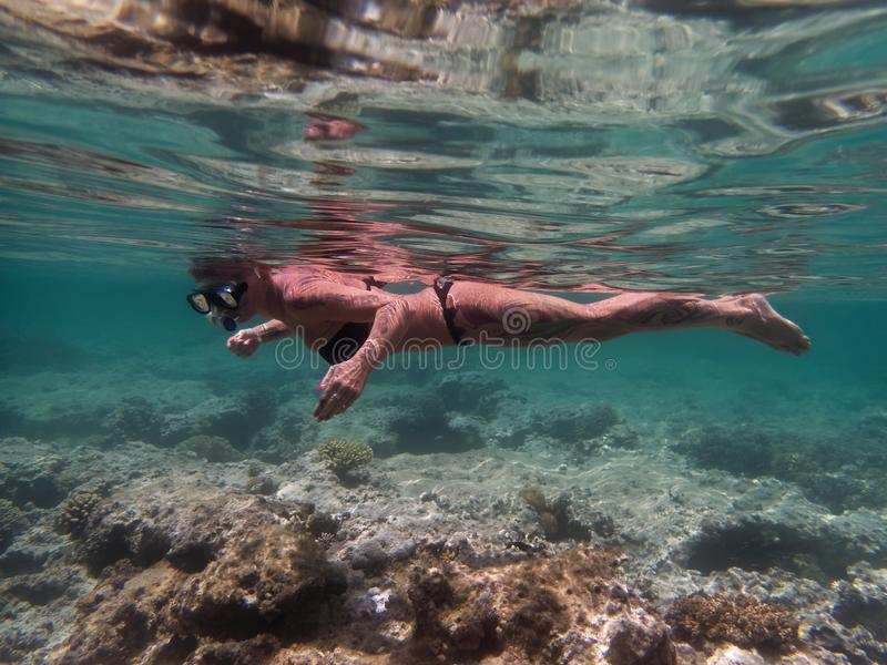 Mature slim sportive woman with tattoos snorkeling. stock photography