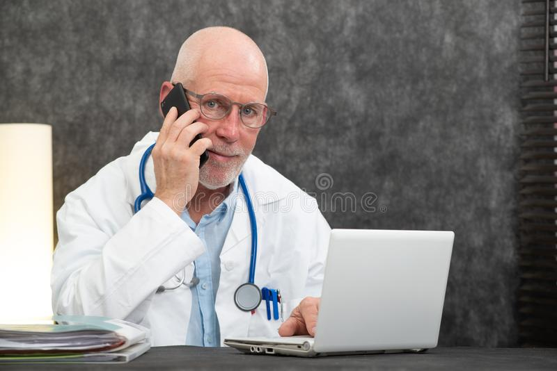 Mature smiling bearded doctor talking on phone stock photo
