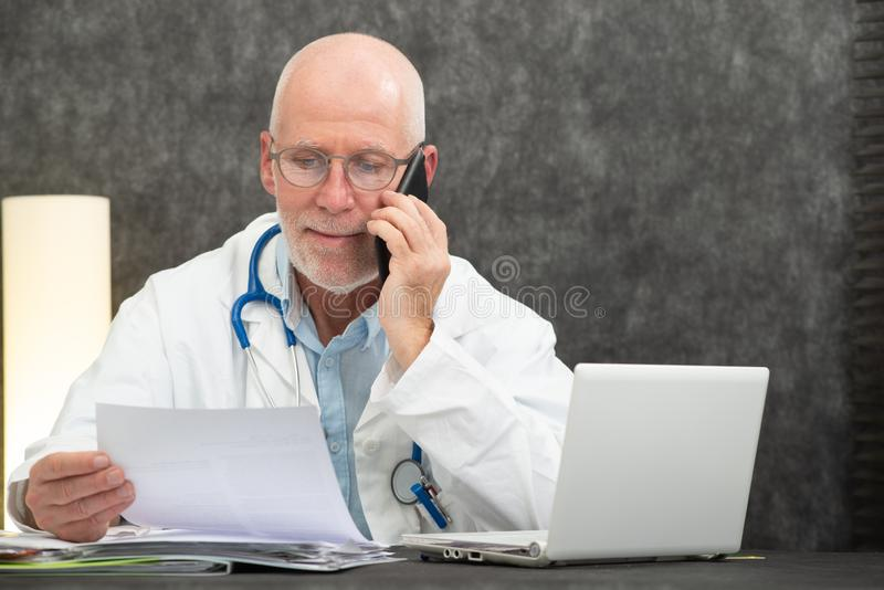 Mature smiling bearded doctor talking on phone. Mature smiling bearded doctor talking on a phone stock images