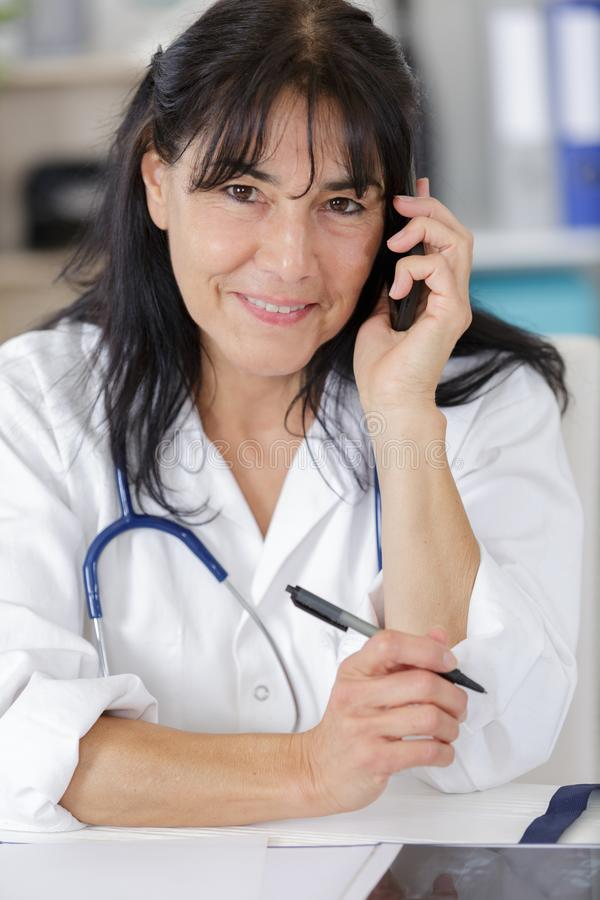 Mature smiling female doctor on phone stock images