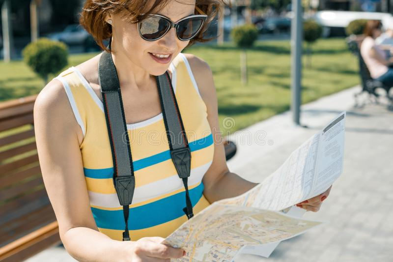 Mature smiling woman with city map and camera, female traveling on a summer sunny day stock photo