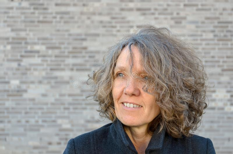 Mature smiling woman with curly tousled hair. Looking off to the side as she poses in front of a grey brick wall with copy space stock images