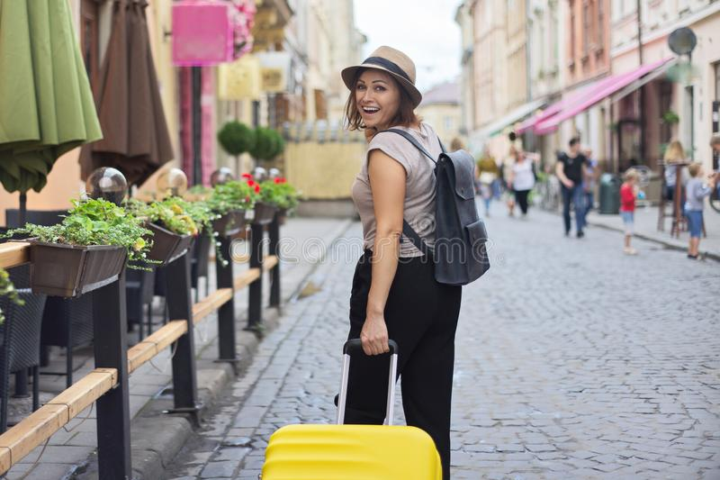 Mature smiling woman traveling in tourist city with suitcase stock photography