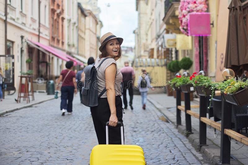 Mature smiling woman traveling in tourist city with suitcase royalty free stock image
