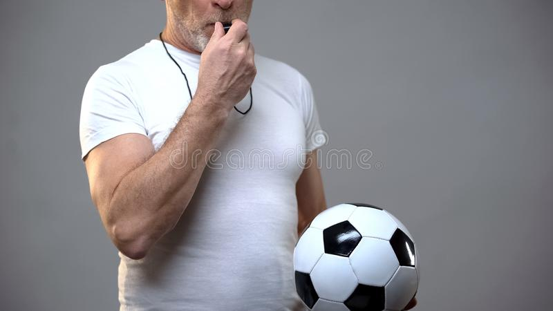Mature sportive man holding football ball and blowing whistle, coach, training stock photography
