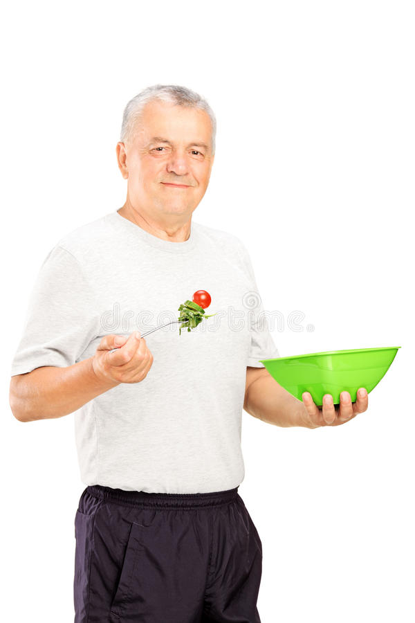 Mature sports man eating a healthy food. A mature sports man eating a healthy food isolated on white background royalty free stock image