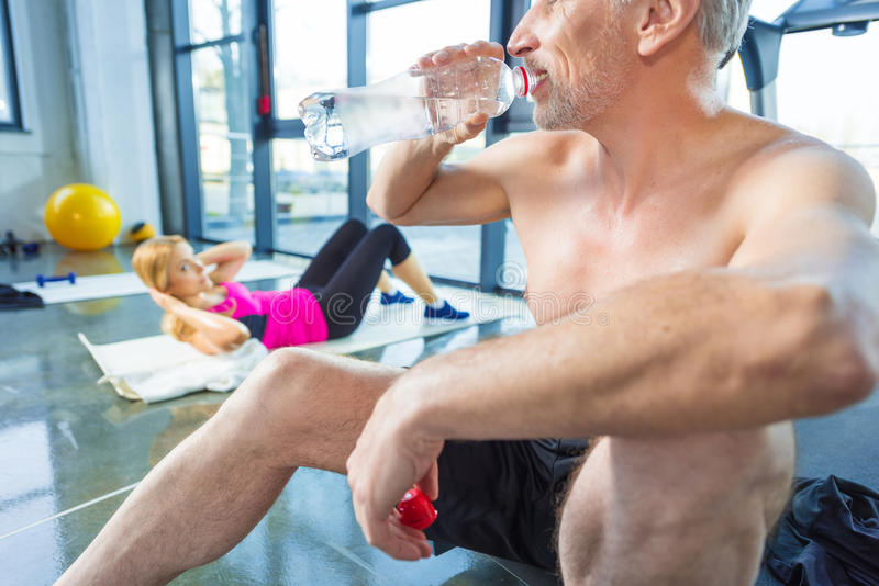 Mature sportsman drinking water while blonde woman doing abs in gym stock image