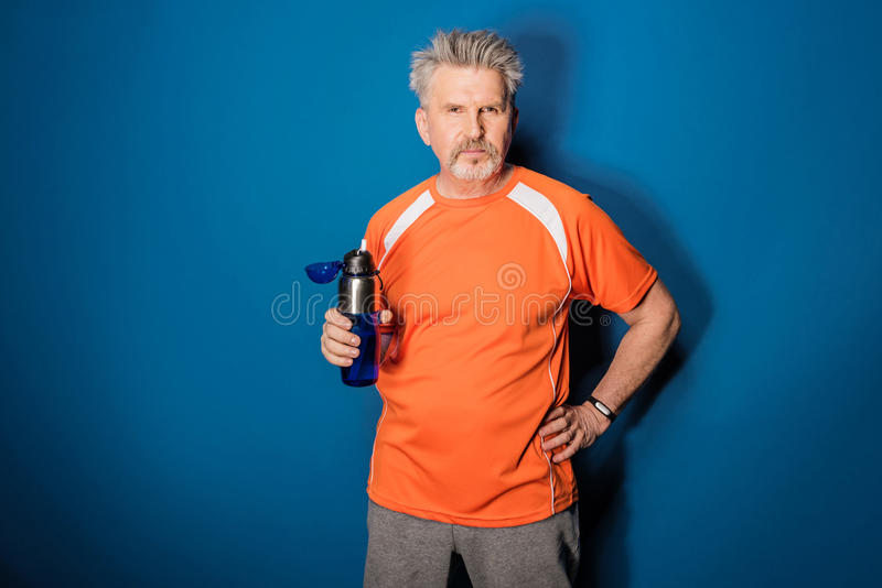 Mature sportsman holding bottle of water and looking at camera royalty free stock photo
