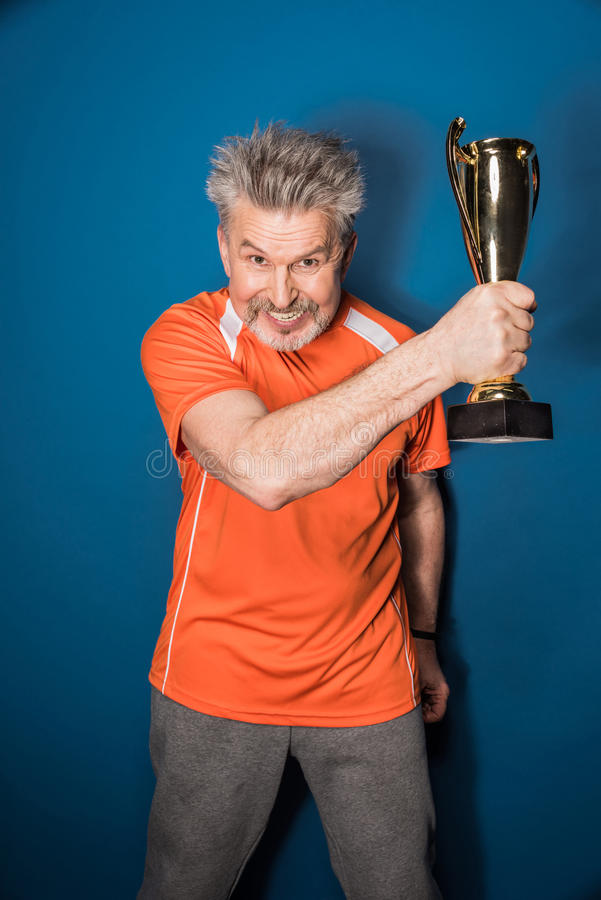 Mature sportsman holding trophy cup isolated on blue stock image
