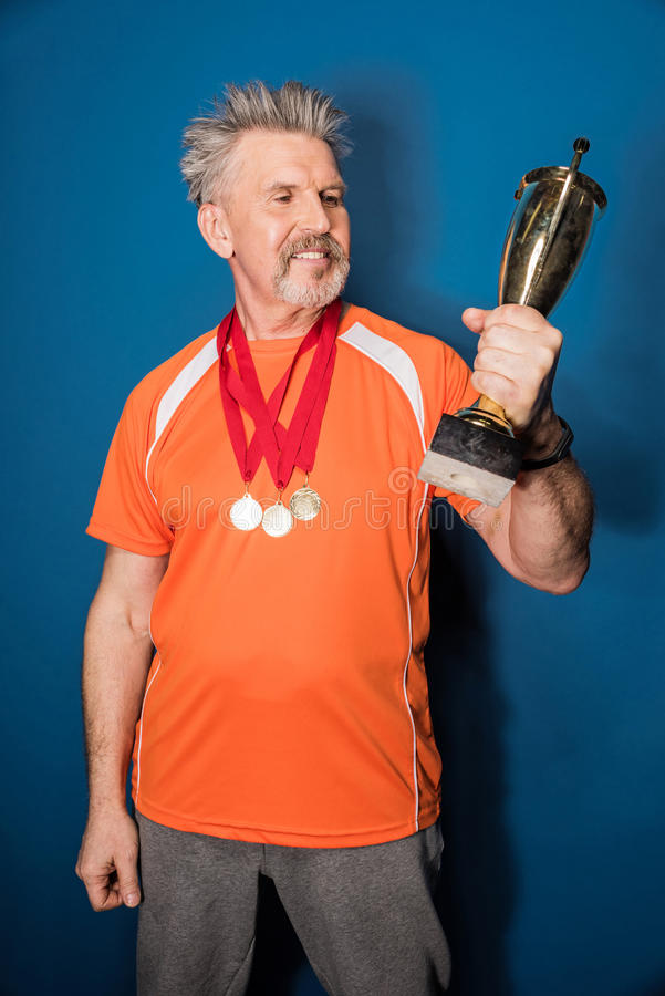 Mature sportsman with medals holding trophy cup on blue stock photography