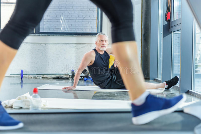 Mature sportsman sitting on yoga mat and looking at woman training on treadmill stock image