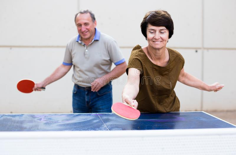 Happy mature spousesn playing table tennis stock images