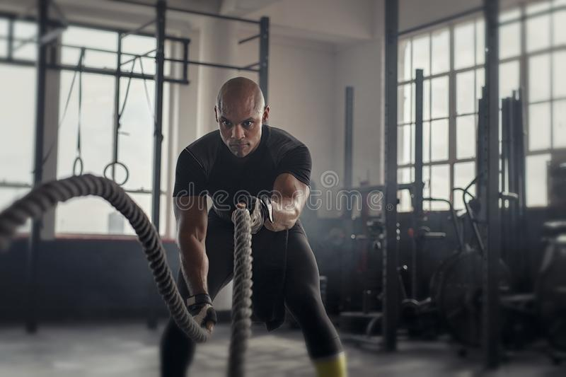 Mature strong man battling with rope royalty free stock images
