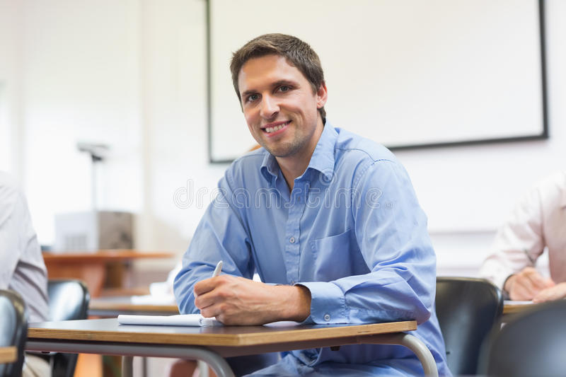 Mature student taking notes in classroom stock photos