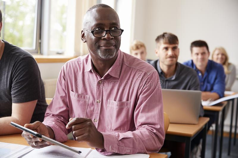 Mature Student Using Digital Tablet In Adult Education Class stock photos