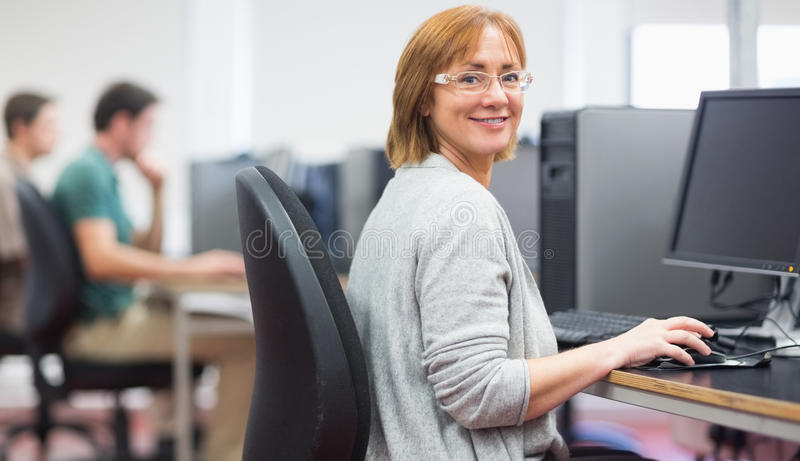 Mature students in the computer room. Portrait of a smiling women by other mature students using computers in the computer room royalty free stock photography
