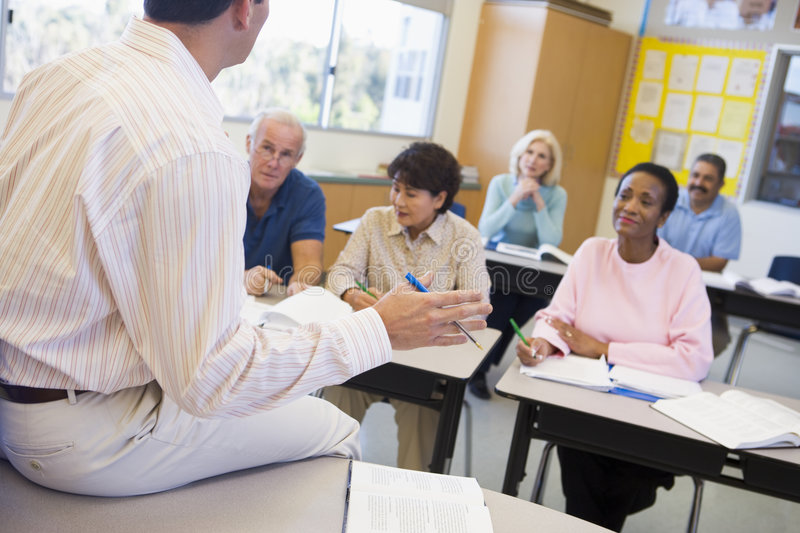 Mature students and their teacher in a classroom royalty free stock images