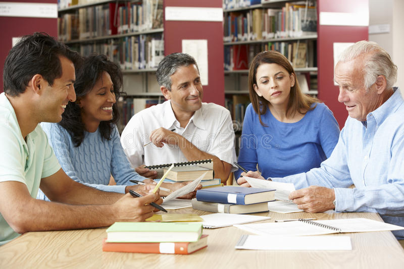 Mature students working in library stock photography