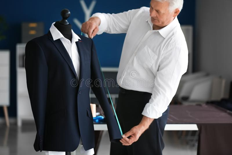 Mature tailor taking measurements of male jacket on mannequin in atelier royalty free stock photos