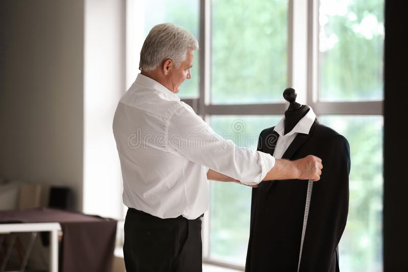 Mature tailor taking measurements of male jacket on mannequin in atelier royalty free stock images