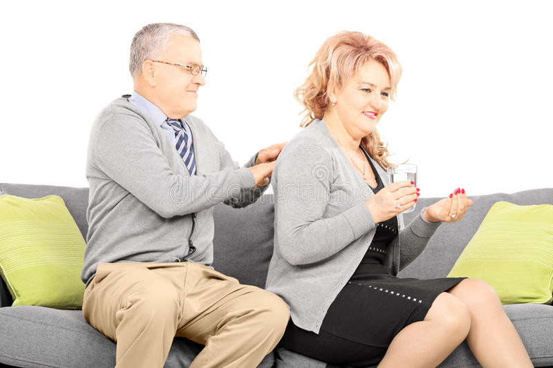 Mature taking pills and husband giving her a back massage royalty free stock image