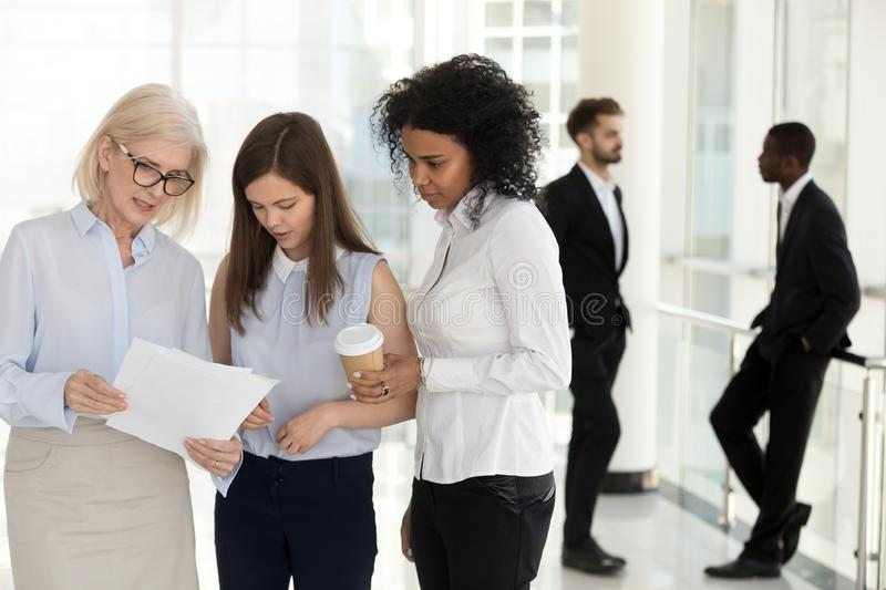 Mature team leader and young employees discussing paperwork in o royalty free stock photos