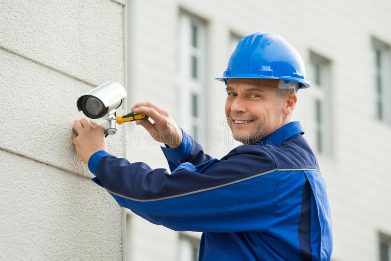 Mature Technician Installing Camera On Wall With Screwdriver stock image