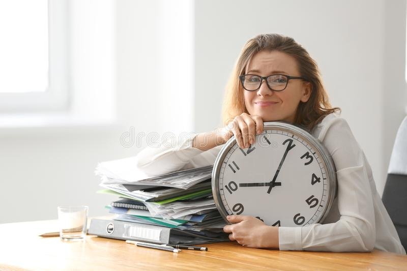 Mature tired woman with clock at table in office. Time management concept royalty free stock photography