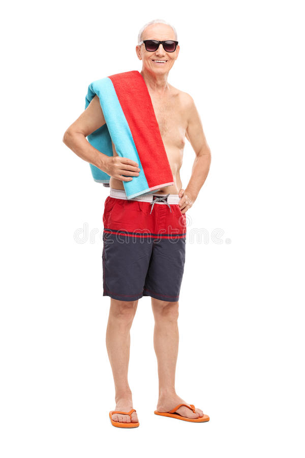 Mature tourist in swim trunks holding a towel. Full length portrait of a mature tourist in swim trunks holding a towel and looking at the camera isolated on stock photo