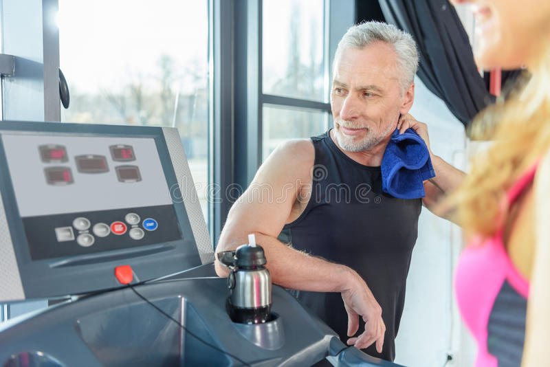 Mature trainer with towel looking at sporty woman exercising on treadmill royalty free stock photography