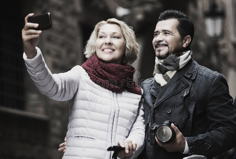 Mature travellers making selfie stock photography