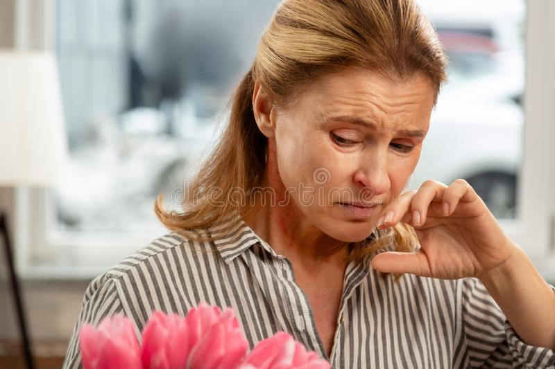 Mature wife feeling sick and allergic to flower blossom royalty free stock images