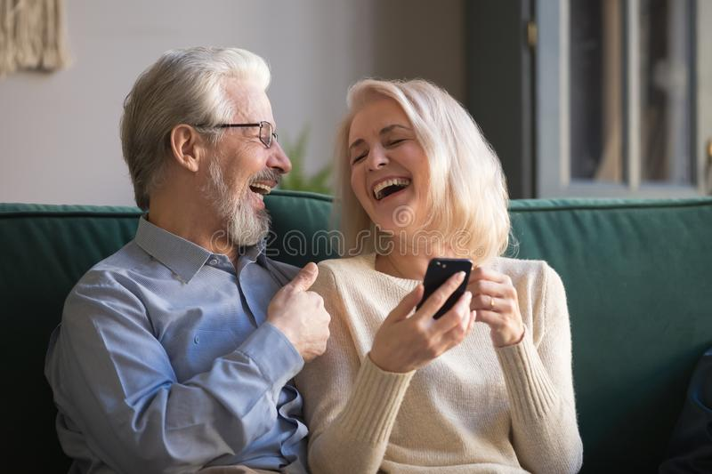 Mature wife and husband, family having fun together, using phone. Middle aged men and women reading funny news in social network, elderly couple laughing royalty free stock image