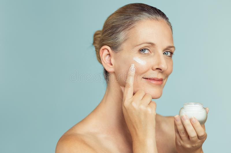 Mature woman applying skin cream on face. Beautiful mature woman holding jar of skin cream for face and body isolated on grey background. Happy senior woman royalty free stock photos