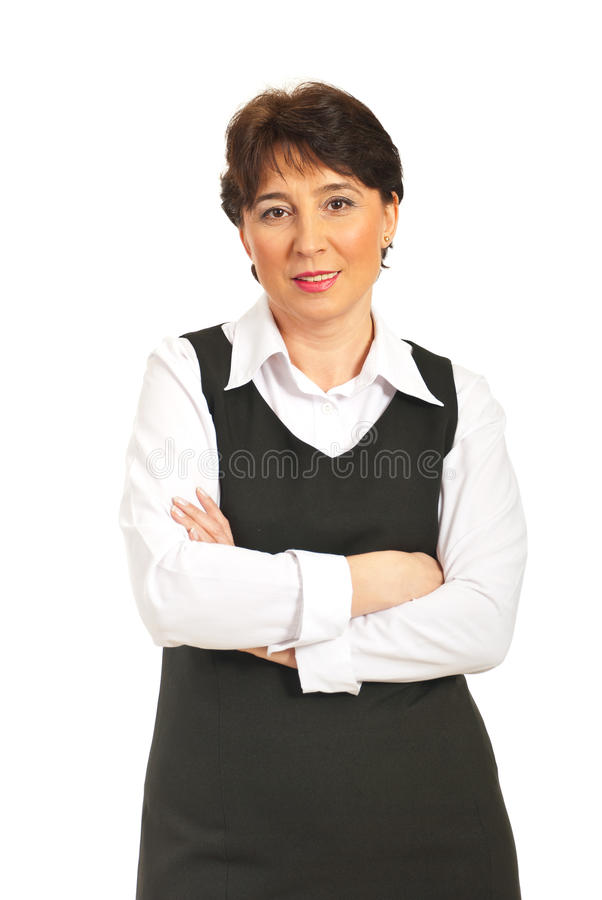 Mature woman with arms folded. Smiling mature business woman standing with arms folded isolated on white background royalty free stock photos