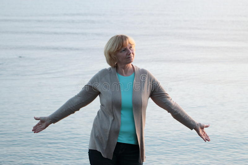 Mature woman with arms outstretched stock image