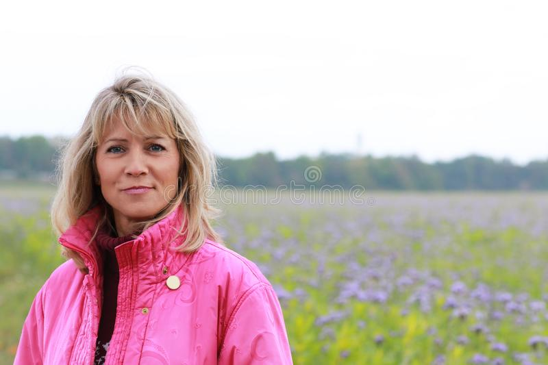 Mature woman in autumn. With jacket in front of flower field stock image