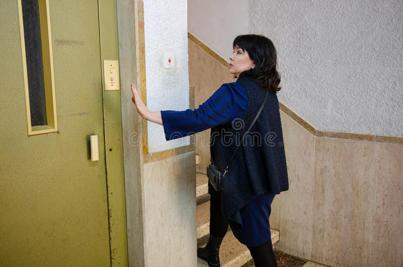 Mature woman avoids the elevator due to claustrophobia stock photography