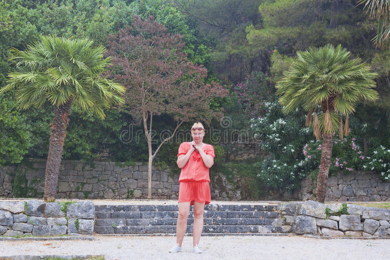A mature woman on the background of park near the island of Sveti Stefan. Summer, 2017 stock photography
