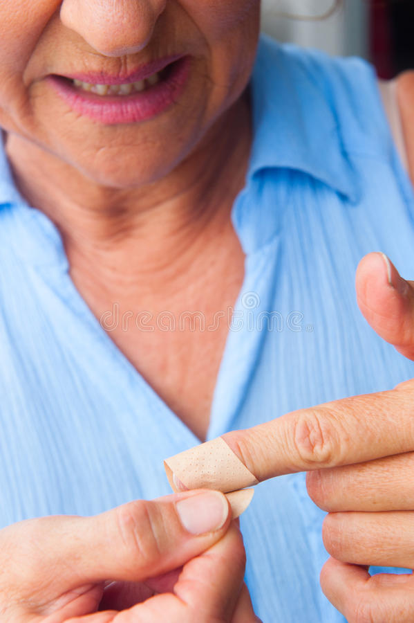 Mature Woman band aid blood finger wound. Portrait mature woman in pain, hurt and suffering, close up of band aid on injured, cut finger wound stock photos
