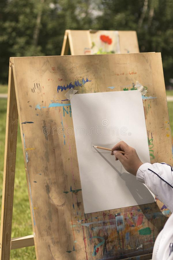 Mature woman begins to draw outdoors in art studio. For elderly people in sunny day. Female hand and paper on easel. Topic for hobby for retired people, social stock photos