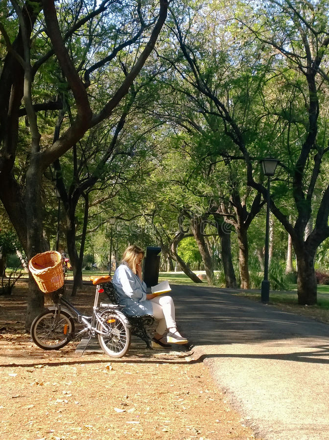 Mature woman with bicycle, reading on a bench in a park royalty free stock photo